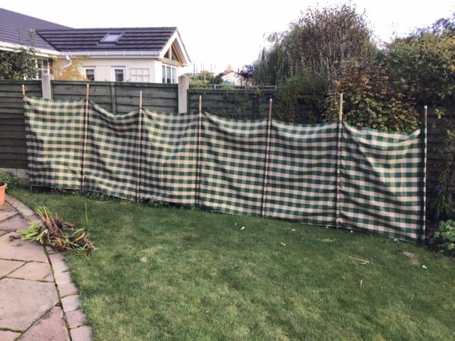 Green and yellow checked Windbreak  with wooden poles